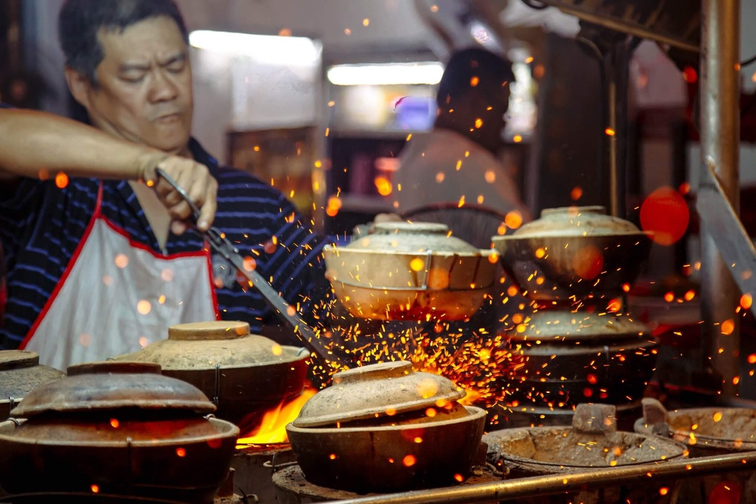 Photo: A cook handling made-to-order clay pot dishes in Kuala Lumpur